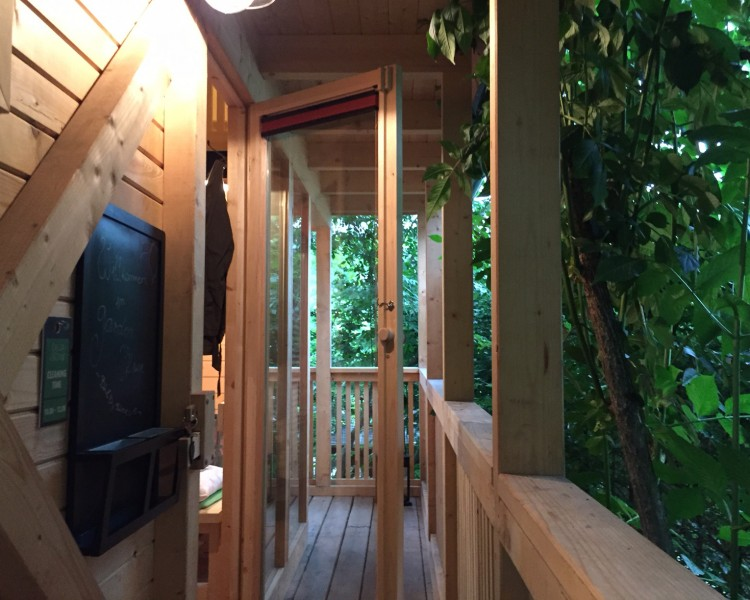 Balkony of a treehouse in the green resort Garden Village Bled