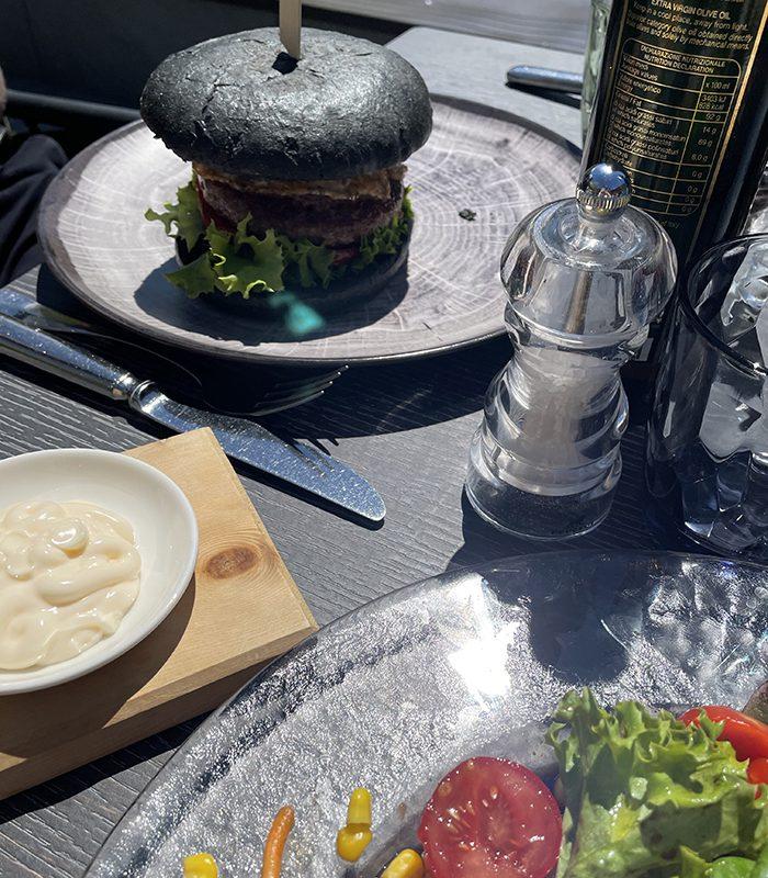 Florens erstes Lunch Gericht? Der Aktivkohle-Burger auf der Sonnenterrasse